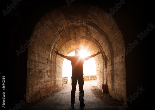 Fotografia, Obraz  Man stands inside of old dark tunnel