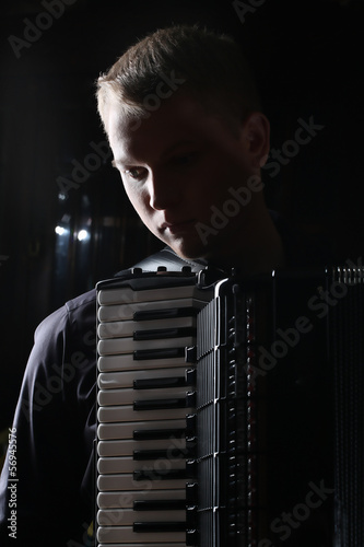 Fotografia, Obraz  musician plays the accordion against a dark background