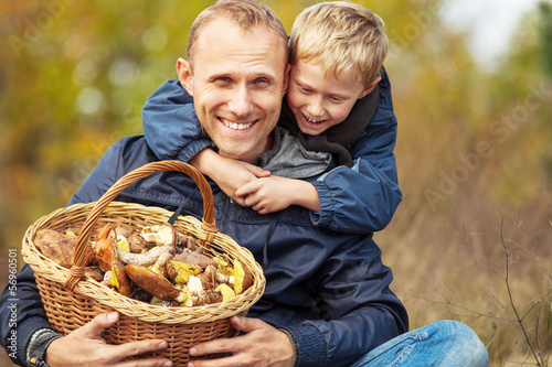 Obraz na płótnie Father and son are happy they have found a basket of mushrooms