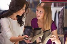 Two Beautiful Young Girls Choosing Shoes At Store