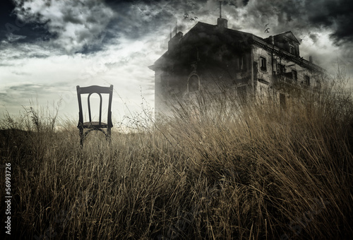 Photo  Abandoned chair out in a field facing a haunted house