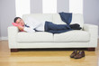 Calm attractive businessman lying on couch
