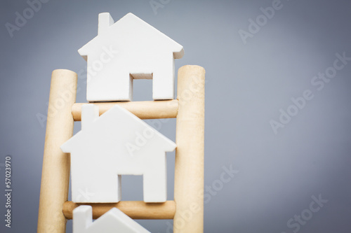 Fotografia  Model Houses On Rungs Of Wooden Property Ladder