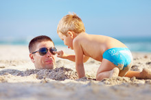 Father And Son Having Fun In Sand On The Beach