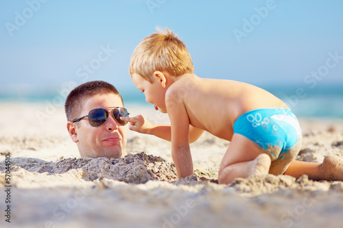 Valokuva  father and son having fun in sand on the beach