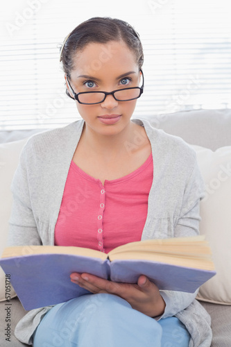 Fotografía  Serious woman with reading glasses sitting on sofa and holding a