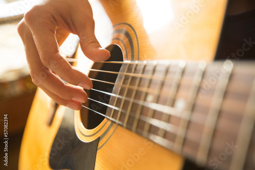 Female hand playing on acoustic guitar. Close-up. Fototapet