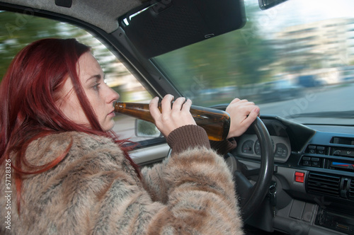 Fotografija Drunk woman driving car with beer in hand