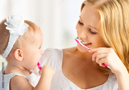 Fotografie, Obraz  mother and daughter baby girl brushing their teeth together