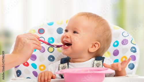 happy mother feeds funny  baby from  spoon Fototapeta