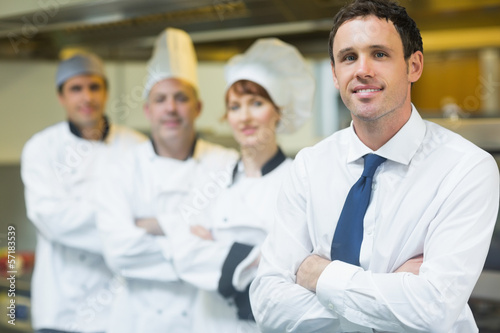 Fotografie, Obraz  Young restaurant manager posing in front of team