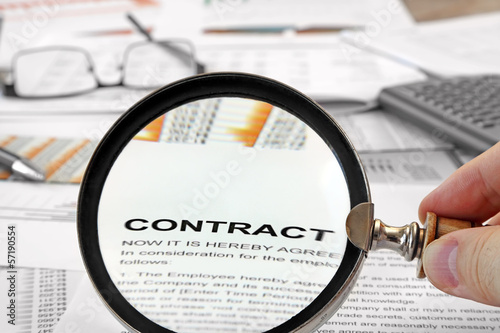Fotografía  Magnifying Glass Over Contract Papers