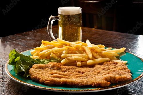 Fotografía cotoletta alla milanese con patate fritte e birra