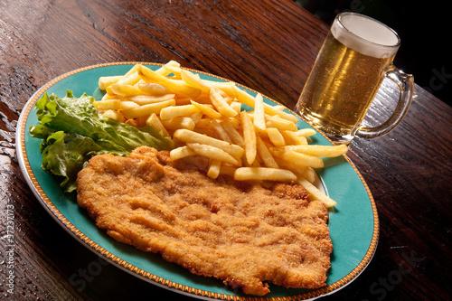 Photo  cotoletta alla milanese con patate fritte e birra