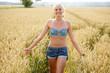 canvas print picture - Junge Frau geht durch ein Kornfeld