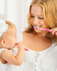 Fototapeta mother and daughter baby girl brushing their teeth together