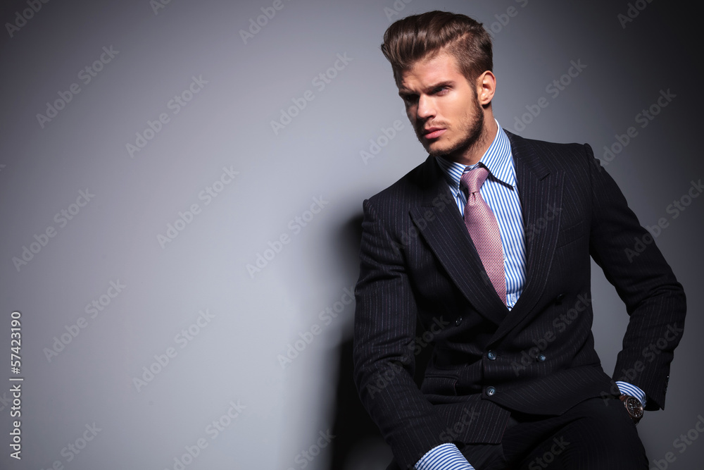 Fototapeta seated young fashion model in suit looks away