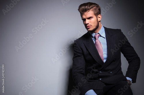 Fotografia seated young fashion model in suit looks away
