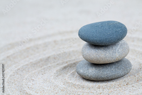 Photo Stands Stones in Sand stone pyramid on sea sand
