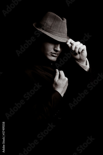 Obraz na plátně  Portrait of young gangster with hat in the darkness