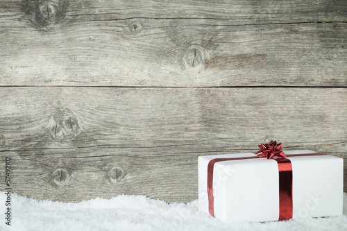 Fotografie, Obraz  Gift box on an old wooden background with snowflake