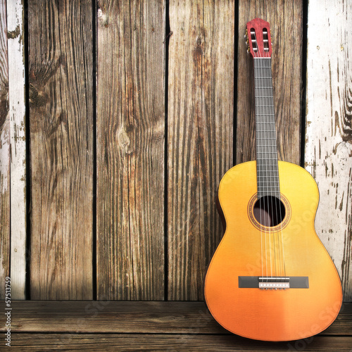 Fotografie, Obraz  Acoustic wooden guitar leaning on a wooden fence.