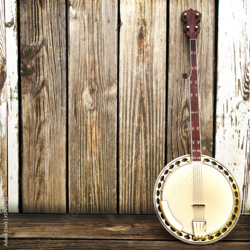 Photo Banjo leaning on a wooden fence. Room for advertisment