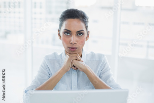 Fotografía  Stern businesswoman sitting at her desk looking at camera