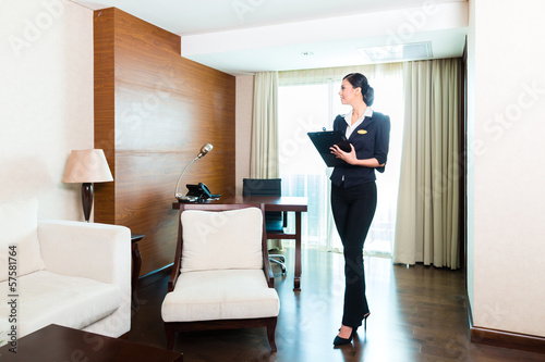 Cuadros en Lienzo Asian executive housekeeper controlling hotel room
