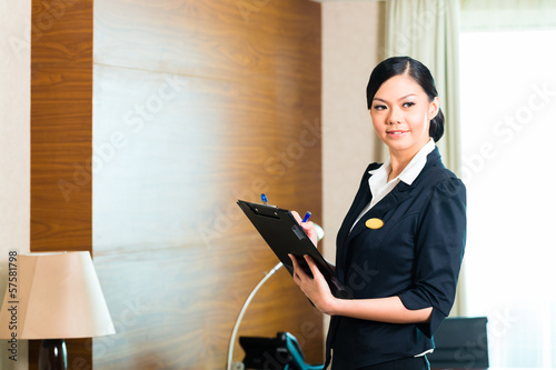 Fotomural Asian executive housekeeper controlling hotel room
