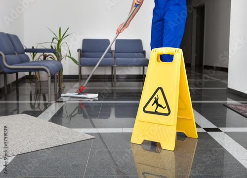 Fotografía  Man With Mop And Wet Floor Sign