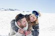 Close-up of a cheerful couple with ski goggles on snow