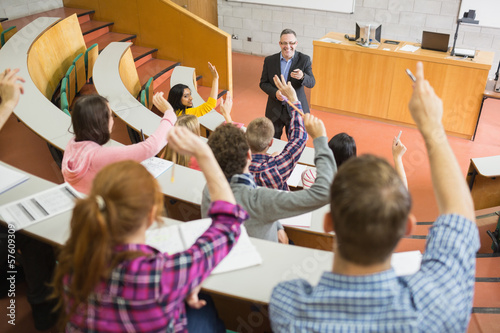 Photographie Students raising hands with teacher in the lecture hall
