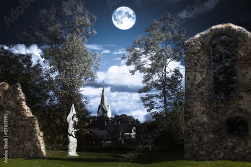 In de dag Volle maan Full moon over an angel statue and castle ruins