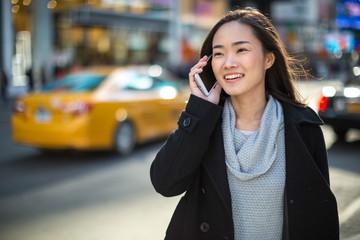 Fototapeta Asian woman in New York City talking on cellphone