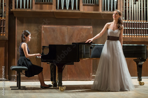 Fototapeta Woman pianist plays piano and singer stands next