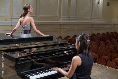Photo Woman pianist sits at piano and singer stands next