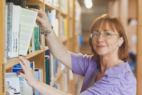 Photographie  Mature female librarian taking a book off a shelf