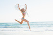 Happy slender woman jumping in the air holding shawl