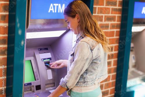 Obraz na plátne Pretty brunette student withdrawing cash