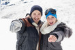 Cheerful couple in jackets pointing at camera on snow covered la