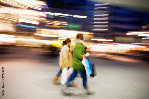 Fotografie, Obraz  Two young women shopping in the city at dusk