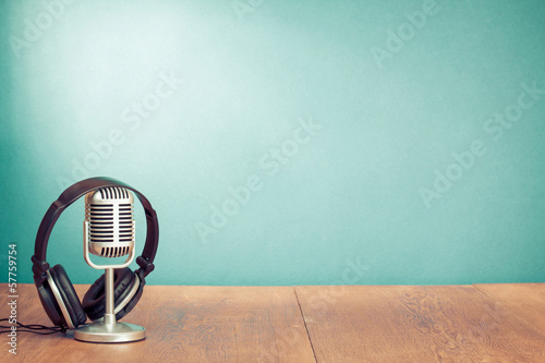 Photo  Retro style microphone, headphones in front aquamarine wall