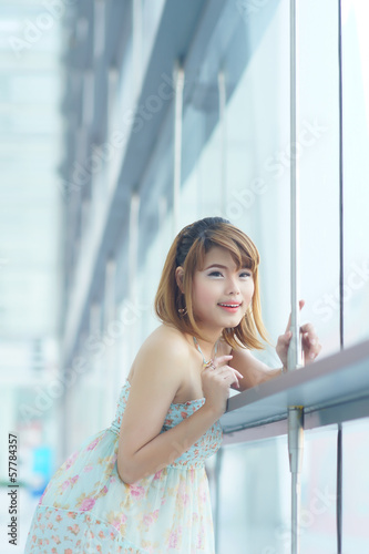 Photo  Young beautifull woman stand near glass wall in office
