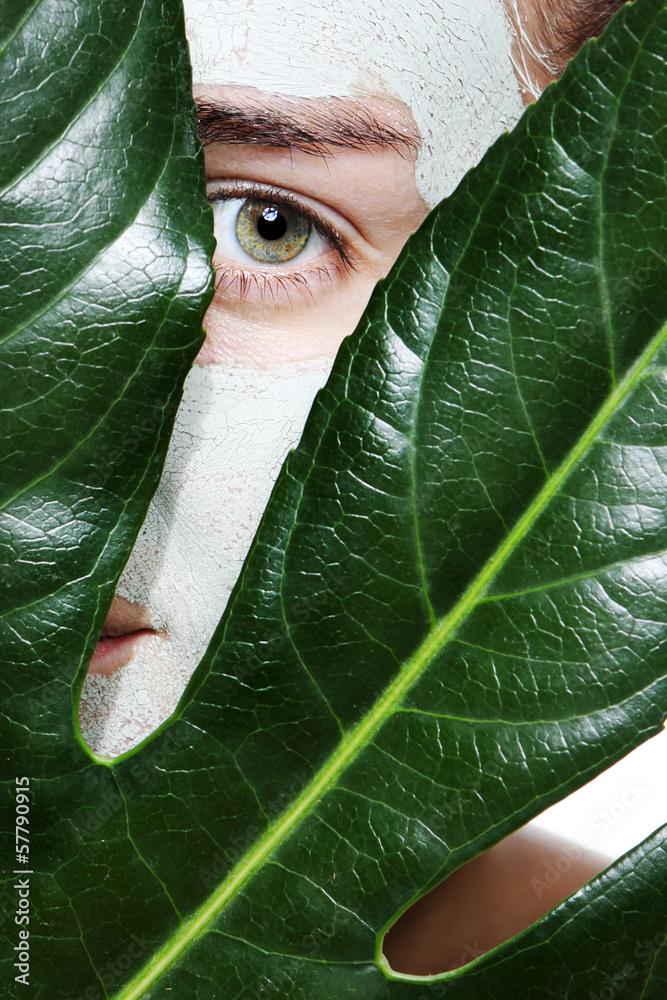 Fototapeta kobieta z liściem w maseczce z zielonej glinki