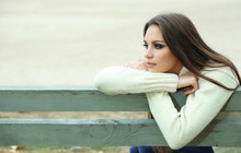 Young Lonely Woman On Bench In Park