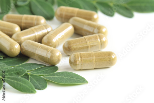 Fotografia  Moringa oleifera capsule with green fresh leaves on white backgr