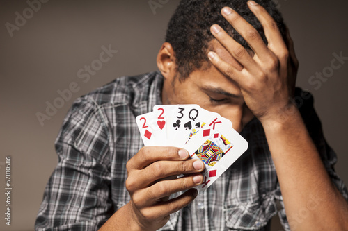 young dark-skinned man shows bad poker cards Canvas Print