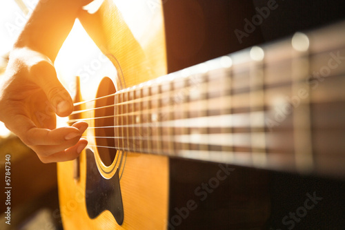 Female hand close-up playing on acoustic guitar. Fototapeta