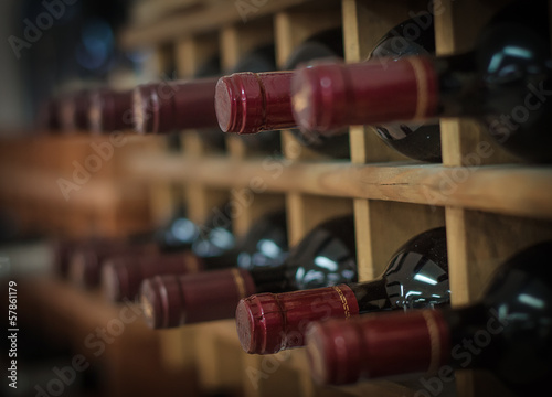 Fotografering  Red wine bottles stacked on wooden racks